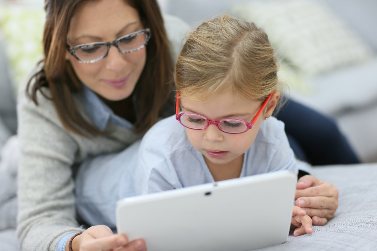 Mother and daughter with eyeglasses playing with tablet a7ab372ece